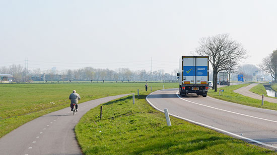 A cycle path in the Dutch countryside. A road with large lorries on it, with a bi-directional cycleway on both sides of the road, each separated by a large grassed area.