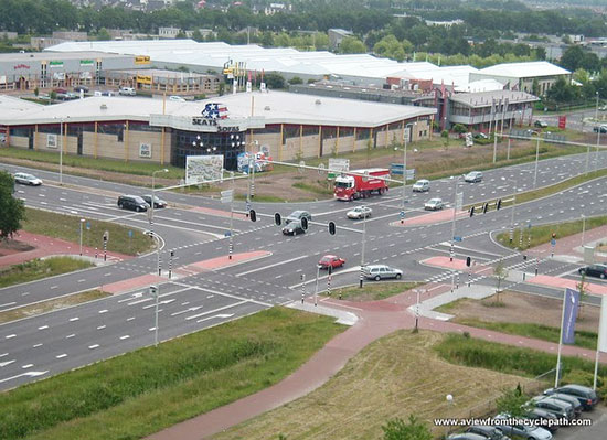 A bird's eye view of a large junction in the Netherlands, showing multi-lane motor traffic with separate cycleways.