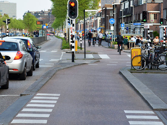 A cycleway changes from regular cycleway height down to carriageway level at the main junction ahead, but the change is so smooth that it is almost imperceptible.