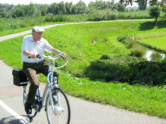 An elderly man uses a practical bicycle for transport in the Dutch countryside.