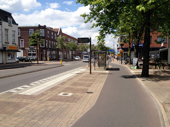 A bus stop in Utrecht. The cycleway passes behind the bus stop, which is on a wide island next to the road.