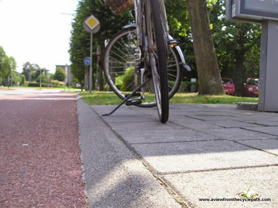 Cat-eye view of a bike next to a forgiving kerb, shallow and angled for safety.