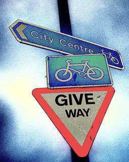 A photo of road signs, including a cycle sign and a cycling direction sign