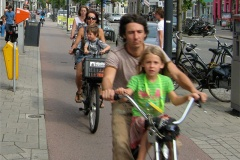 A family cycling along a cycle path in Utrecht. The young children are sat on child seats mounted behind the handlebars.