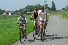 A family riding their bikes on a cycle path in the countryside