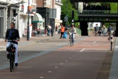 People ride their bikes along a wide cycle path
