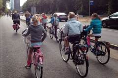 A wide cycle path alongside (but physically separate from) a road. A group of children ride bikes, their bags in the crates attached to the front.