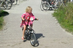 A little girl rides her bike out of a bike parking lot at the beach and onto a cycle path.