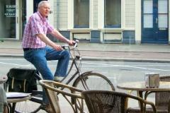 A middle-aged man rides his bike along a cycle path past a café