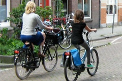 A mother and her young daughter ride their bikes