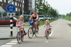 A mother and her two young daughters ride their bikes on a wide cycle path