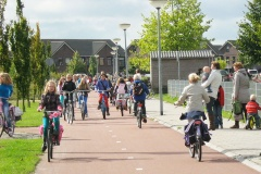 A wide cycle path with footpath alongside, dozens of children riding bikes