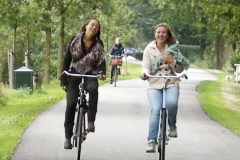 Two women ride bikes side-by-side, laughing as they go