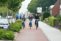 Three boys ride alongside each other on a cycle path. They are separated from the road by parking and trees.