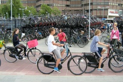 "Three teenagers on Dutch ""omafiets"" bikes ride past hundreds of bikes parked in racks"