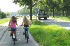 Two girls use a cycle path which is separated from the busy road by a wide grass verge and trees