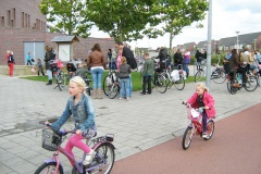 Two young girls ride home from school using a cycle path. Other children and parents stand and talk by their bikes on the footpath in the background.