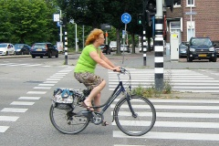 A middle-aged woman rides her bike. No safety accessories needed!