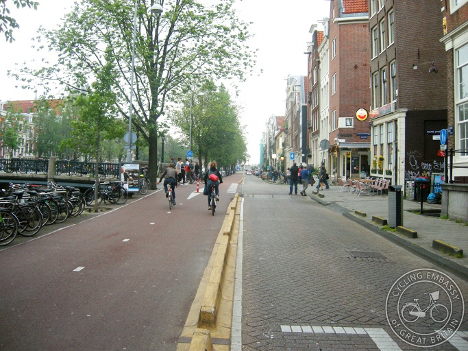 A photo of Geldersekade in Amsterdam. On the left is a wide two-way cycle path. On the right is a one-way road for cars.