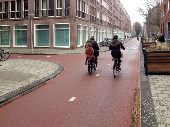 Two parents cycle with their young child along a cycling-and-walking-only street in Amsterdam.