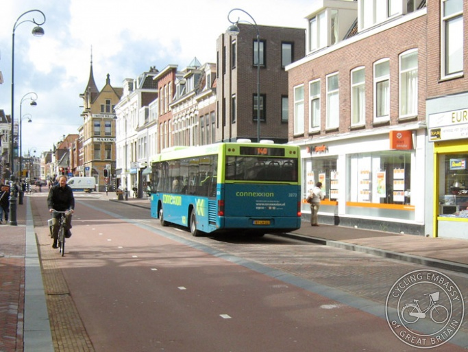 A photo of Kruisweg in Haarlem. A two-way road with parking has been converted into a one-way bus road with a wide two-way cycle path alongside but separated by a gentle curving kerb.