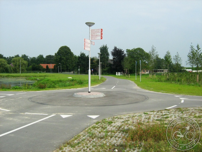 Four cycle paths come together and are joined by a roundabout with directional signage