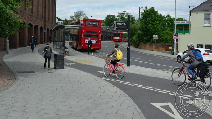Cyclists riding behind a bus stop shelter on a bus stop bypass cycle track, Vogue gyratory, Brighton
