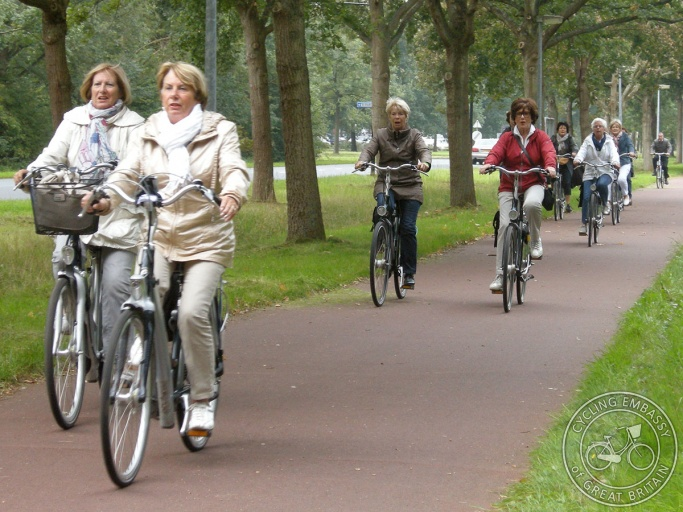 Middle-aged women riding on a cycle path which is separated from the road by a wide grass verge and two rows of trees