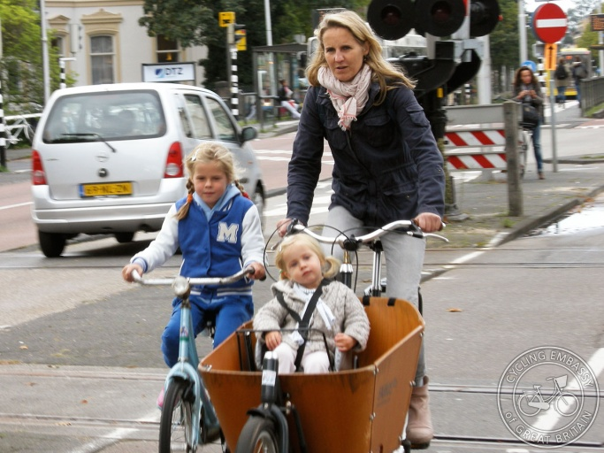 A mother rides a bakfiets (box-bike) in which her youngest daughter sits. Her older daughter rides her own bike alongside.