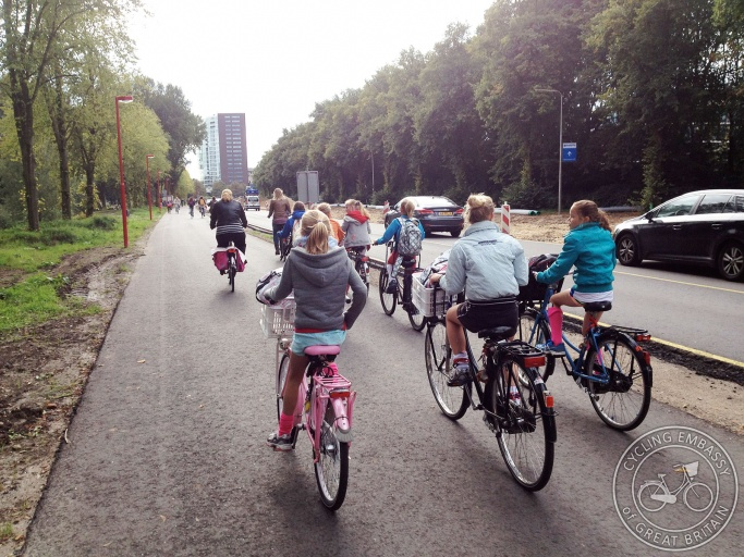Many children and adults ride bikes on a wide cycle path alongside (but physically separate from) the motor-carriageway.
