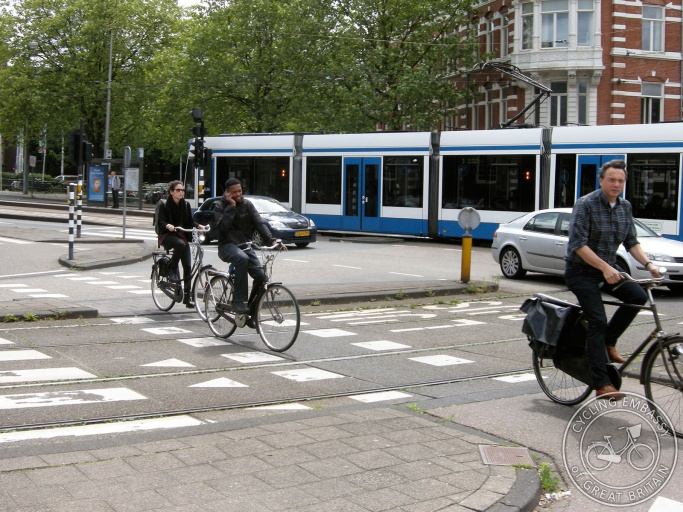 People on bikes in Amsterdam. The cycle path crosses tram tracks at ninety degrees, which means that wheels don't get caught and likelihood of slipping is minimal.