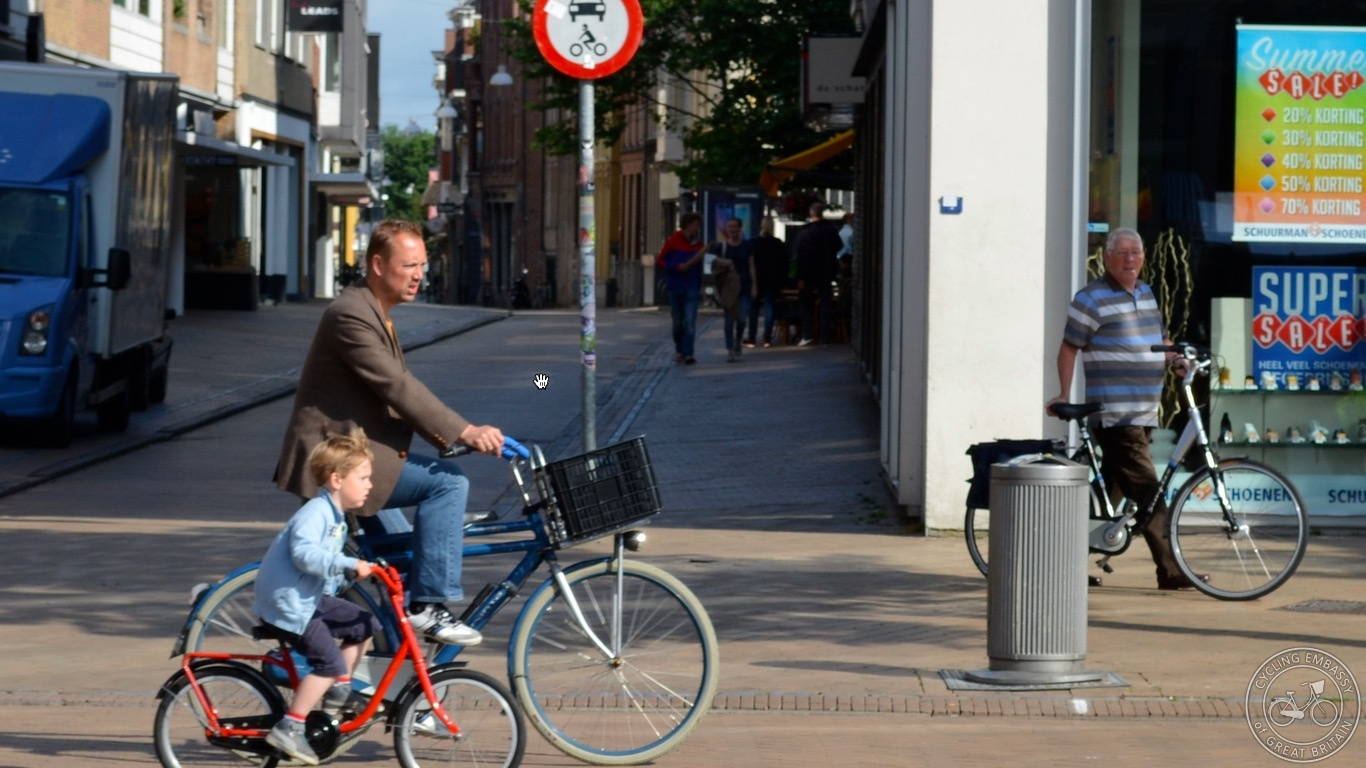 Dad and young son cycling Groningen city centre