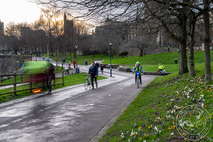 Cyclists and pedestrians on a parallel cycleway and footpath through Castle Park in Bristol