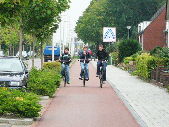 Three boys riding side by side on a red asphalt cycleway, separated from motor traffic by bushes, and with a forgiving, angled kerb up to the footway.