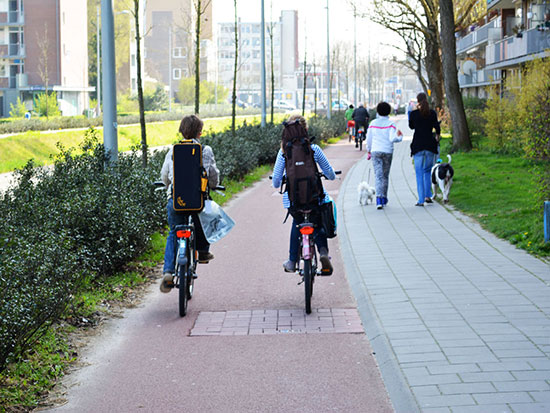 Two boys ride on a protected cycle path in the Netherlands. It has physical separation from motor traffic, and a forgiving kerb between itself and the footway.