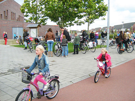 Two young girls ride their bikes home from school on a smooth, wide, motor-free cycleway in the Netherlands.