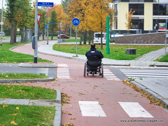 A wheelchair user rides on a Dutch cycleway.